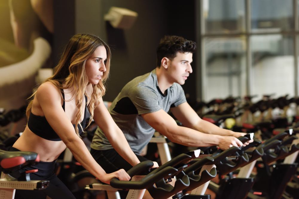 Two people biking in the gym, exercising legs doing cardio workout cycling bikes. Couple in a spinning class wearing sportswear.
